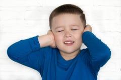 Το νέο αγόρι που φορά τη μπλε ζακέτα με τα μάτια του έκλεισε την κάλυψη των αυτιών του για να ακούσει Στοκ Εικόνες