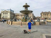 Το νέο αγόρι προετοιμάζεται να πάρει μια φωτογραφία των γονέων του μπροστά από μια πηγή του Παρισιού Στοκ φωτογραφία με δικαίωμα ελεύθερης χρήσης
