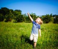 Το νέο αγόρι σε έναν τομέα δείχνει τον ουρανό στοκ φωτογραφία