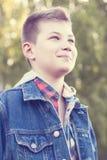 Το νέο αγόρι στέκεται την ηλιόλουστη ημέρα λιβαδιών πάρκων, σακάκι τζιν, το πουκάμισο εξετάζει την απόσταση Στοκ Εικόνες