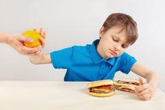 Το νέο αγόρι στον πίνακα επιλέγει μεταξύ του γρήγορου γεύματος και των φρούτων στο άσπρο υπόβαθρο στοκ εικόνα