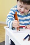 Το νέο αγόρι σύρει με τρία μολύβια Στοκ Φωτογραφία