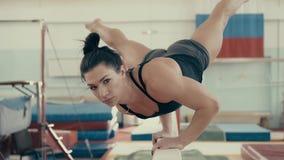 Το νέο αθλητικό κορίτσι σε μια γυμναστική, εκτελεί ένα frieze σε έναν φραγ απόθεμα βίντεο
