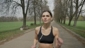 Το νέο αθλητικό κορίτσι τρέχει με τα ακουστικά στο πάρκο το καλοκαίρι, υγιής τρόπος ζωής, αθλητική σύλληψη