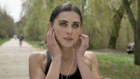 Το νέο αθλητικό κορίτσι φορά τα ακουστικά και τρέχει στο πάρκο, υγιής τρόπος ζωής, αθλητική σύλληψη φιλμ μικρού μήκους