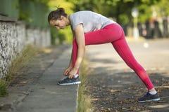 Το νέο αθλητικό κορίτσι δένει τις δαντέλλες στα πάνινα παπούτσια Ικανότητα στοκ εικόνα