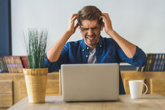 Το νέο αρσενικό freelancer δεν μπορεί να εργαστεί λόγω των πονοκέφαλων Στοκ Φωτογραφία