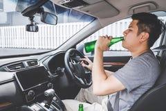 Το νέο ασιατικό άτομο οδηγεί ένα αυτοκίνητο με πιωμένος ένα μπουκάλι της μπύρας πίσω από τη ρόδα ενός αυτοκινήτου στοκ φωτογραφία