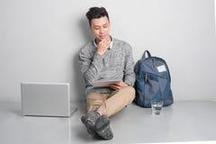 Το νέο ασιατικό άτομο στα περιστασιακά ενδύματα χρησιμοποιεί ένα lap-top, χαμογελώντας το whi Στοκ Φωτογραφίες