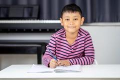 Το νέο ασιατικό αγόρι γράφει στο βιβλίο σημειώσεων από το μολύβι στο δωμάτιο Στοκ Εικόνες
