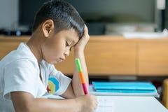 Το νέο ασιατικό αγόρι γράφει στο βιβλίο σημειώσεων από το μολύβι στο δωμάτιο Στοκ φωτογραφία με δικαίωμα ελεύθερης χρήσης