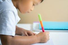 Το νέο ασιατικό αγόρι γράφει στο βιβλίο σημειώσεων από το μολύβι στο δωμάτιο Στοκ εικόνες με δικαίωμα ελεύθερης χρήσης
