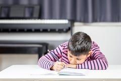 Το νέο ασιατικό αγόρι που κουράζεται γράφει στο βιβλίο σημειώσεων από το μολύβι στο ro Στοκ εικόνα με δικαίωμα ελεύθερης χρήσης