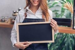 Το νέο ασιατικό θηλυκό barista στην ποδιά τζιν κρατά έναν πίνακα κιμωλίας με ένα όμορφο χαμόγελο στη καφετερία της Στοκ Εικόνα