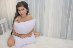 Το νέο ασιατικό κορίτσι έντυσε την προκλητική πρότυπη συνεδρίαση στο κρεβάτι της και το αγκάλιασμα του μαξιλαριού με τα χέρια της στοκ φωτογραφίες