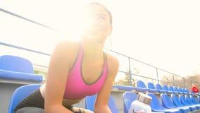 Το νέο ασιατικό κορίτσι αθλητών στηρίζεται τη συνεδρίαση στο στάδιο σε μια ηλιόλουστη ημέρα απόθεμα βίντεο