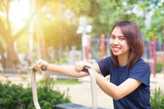 Το νέο ασιατικό χαμόγελο απολαμβάνει τη θωρακική άσκηση στο πάρκο για υγιή Στοκ φωτογραφίες με δικαίωμα ελεύθερης χρήσης