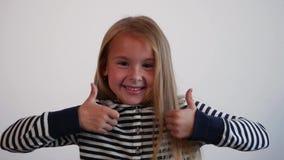 Το νέο αστείο κορίτσι κάνει το σημάδι της επιτυχίας Το κορίτσι στα ριγωτά ενδύματα που γελούν και που παρουσιάζουν φυλλομετρεί επ φιλμ μικρού μήκους