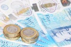 Το νέο βρετανικό πολυμερές σώμα σημείωση πέντε λιβρών και τα νέα 12 πλαισίωσε το νόμισμα £1 Στοκ Φωτογραφία