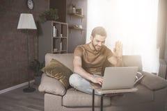 Το νέο γενειοφόρο άτομο έχει τη σε απευθείας σύνδεση συνομιλία στο σπίτι στοκ φωτογραφίες με δικαίωμα ελεύθερης χρήσης