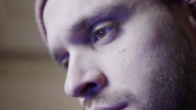 Το νέο γενειοφόρο άτομο κοιτάζει επίμονα στην επίδειξη που απεικονίζει στα καφετιά μάτια του απόθεμα βίντεο