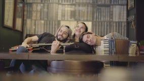 Το νέο γενειοφόρο άτομο με την κιθάρα και ο φίλος του με το ακκορντέον βάζουν τα κεφάλια τους στο στήθος μιας παχιάς συνεδρίασης  απόθεμα βίντεο