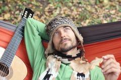 Το νέο γενειοφόρο άτομο με το wistful χαμόγελο και μια κιθάρα χαλαρώνουν σε ένα ζαμπόν στοκ εικόνες με δικαίωμα ελεύθερης χρήσης