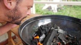 Το νέο γενειοφόρο άτομο φυσά τους άνθρακες στη σχάρα και την αρχική πυρκαγιά Μαύρο ξύλινο κάψιμο ξυλάνθρακα Bbq HD απόθεμα βίντεο