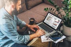 Το νέο γενειοφόρο άτομο hipster, επιχειρηματίας κάθεται στον καναπέ στο τραπεζάκι σαλονιού, χρησιμοποιεί το lap-top με τις γραφικ Στοκ Φωτογραφίες