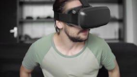 Το νέο γενειοφόρο άτομο hipster χρησιμοποιώντας την επίδειξη κασκών VR του για το παιχνίδι εικονικής πραγματικότητας ή προσέχοντα απόθεμα βίντεο