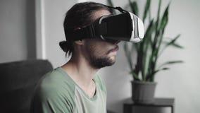 Το νέο γενειοφόρο άτομο hipster χρησιμοποιώντας την επίδειξη κασκών VR του για το παιχνίδι εικονικής πραγματικότητας ή προσέχοντα φιλμ μικρού μήκους