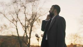 Το νέο γενειοφόρο επιχειρησιακό άτομο στο παλτό που μιλά στο smartphone και που κάνει ασχολείται στην οδό με το φως του ήλιου ανα φιλμ μικρού μήκους