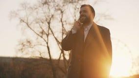 Το νέο γενειοφόρο επιχειρησιακό άτομο στο παλτό που μιλά στο smartphone και που κάνει ασχολείται στην οδό με το φως του ήλιου ανα απόθεμα βίντεο