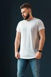 Το νέο γενειοφόρο όμορφο άτομο hipster, που ντύνεται στην άσπρη μπλούζα με τα κοντά μανίκια και τα τζιν, στέκεται στο εσωτερικό στοκ εικόνες με δικαίωμα ελεύθερης χρήσης
