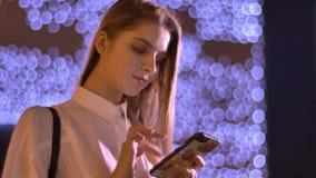 Το νέο γλυκό κορίτσι δακτυλογραφεί στο smartphone της το βράδυ το καλοκαίρι, έννοια επικοινωνίας Φω'τα στο υπόβαθρο απόθεμα βίντεο