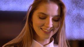 Το νέο γλυκό κορίτσι είναι προσέχει στη κάμερα το βράδυ το καλοκαίρι, χαμόγελο, φω'τα στο υπόβαθρο απόθεμα βίντεο