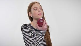 Το νέο γλυκό κορίτσι πιπεροριζών δαγκώνει το κόκκινο μήλο, το προσφέρει, έννοια επικοινωνίας, άσπρο υπόβαθρο απόθεμα βίντεο