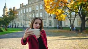 Το νέο ελκυστικό θηλυκό studend που κάνει ένα selfie σε διαφορετικό θέτει μπροστά από το πανεπιστήμιο σε μια ηλιόλουστη ημέρα φιλμ μικρού μήκους