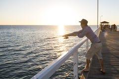 Το νέο ελκυστικό και ευτυχές άτομο στο πουκάμισο και το καπέλο που αλιεύει στη θάλασσα παραλιών ελλιμενίζουν τη χρησιμοποίηση του Στοκ Εικόνα