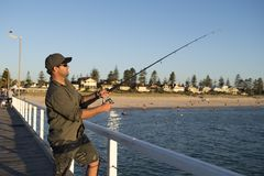 Το νέο ελκυστικό και ευτυχές άτομο στο πουκάμισο και το καπέλο που αλιεύει στη θάλασσα παραλιών ελλιμενίζουν τη χρησιμοποίηση του Στοκ φωτογραφίες με δικαίωμα ελεύθερης χρήσης