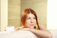 Το νέο ελκυστικό κορίτσι κρατά την κενή άσπρη κάρτα Στοκ εικόνα με δικαίωμα ελεύθερης χρήσης