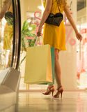 Το νέο ελκυστικό κορίτσι στα κόκκινα τακούνια στο κίτρινο φόρεμα περπατά στη λεωφόρο με τις τσάντες αγορών Στοκ Φωτογραφίες