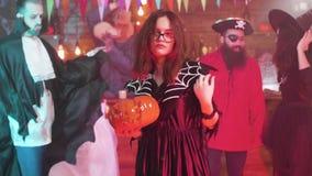 Το νέο ελκυστικό κορίτσι στο κοστούμι μαγισσών χορεύει με ένα Jack-ο-φανάρι στα χέρια της απόθεμα βίντεο