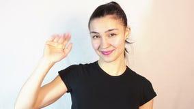 Το νέο ελκυστικό κορίτσι χαμογελά και κύματα τους καλωσορίζοντας φίλους χεριών απόθεμα βίντεο