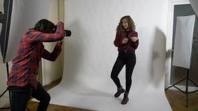 Το νέο ελκυστικό πρότυπο μόδας ντυμένος στο κόκκινο χτύπημα θέτει και το κτύπημα της σγουρής ξανθής τρίχας της σε σε αργή κίνηση  απόθεμα βίντεο
