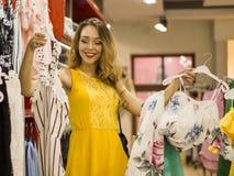 Το νέο ελκυστικό χαμογελώντας κορίτσι στο κίτρινο φόρεμα είναι επιλέγει το φόρεμα μόδας στη λεωφόρο Στοκ Φωτογραφία