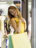 Το νέο ελκυστικό χαμογελώντας κορίτσι στο κίτρινο φόρεμα περπατά στη λεωφόρο με τις τσάντες αγορών Στοκ εικόνα με δικαίωμα ελεύθερης χρήσης