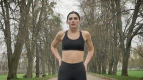 Το νέο εξαντλημένο αθλητικό κορίτσι παίρνει ένα υπόλοιπο και συνεχίζει στο πάρκο το καλοκαίρι, υγιής τρόπος ζωής, αθλητική σύλληψ φιλμ μικρού μήκους