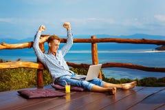 Το νέο επιτυχές άτομο κάθεται με το lap-top στοκ εικόνα