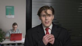 Το νέο επιτυχές άτομο σε ένα κοστούμι παρουσιάζει φοβισμένος, εκφοβισμένος, φοβισμένος, φόβος Εργασίες ατόμων για έναν υπολογιστή φιλμ μικρού μήκους